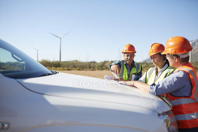 Engineers reviewing blueprint on truck at sunny wind turbine power plant — Stock Photo