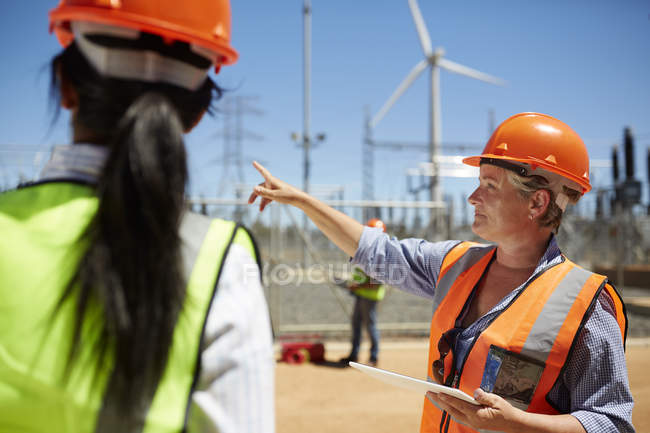 Female engineer with digital tablet talking to colleague at wind turbine power plant — Stockfoto