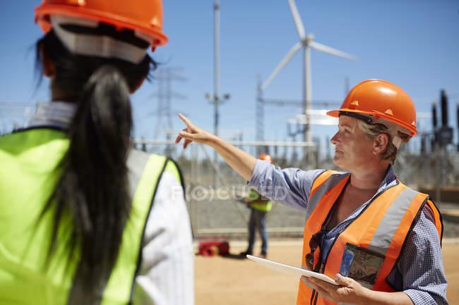 Ingeniera con tableta digital hablando con el colega en planta de energía de la turbina de viento - foto de stock