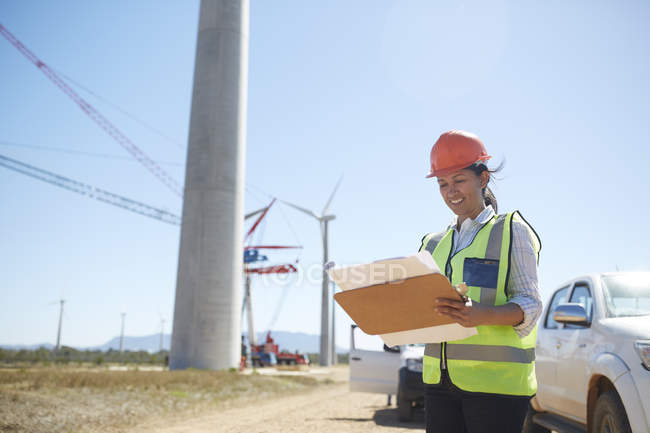 Smiling female engineer with blueprint at sunny wind turbine power plant — Stock Photo