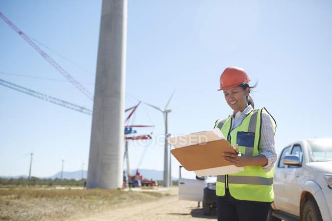 Улыбающиеся женщина инженер с планом на Солнечный ветер турбины электростанции — стоковое фото