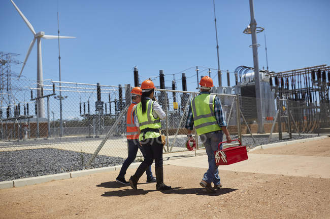Engineers with toolbox walking at sunny wind turbine power plant — Stock Photo