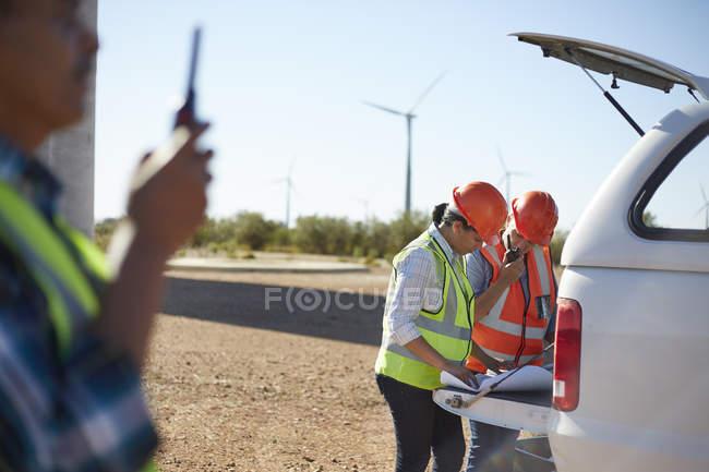 Инженеры, обзор чертежи на грузовик на Солнечный ветер турбины электростанции — стоковое фото