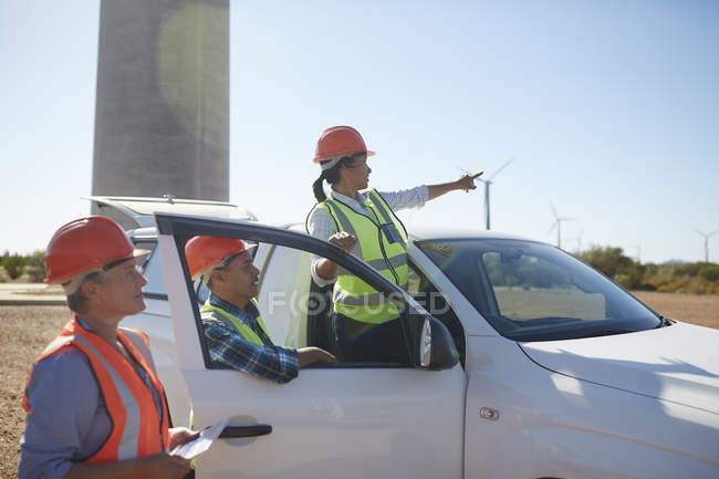 Engineers at truck at sunny wind turbine power plant — Stock Photo
