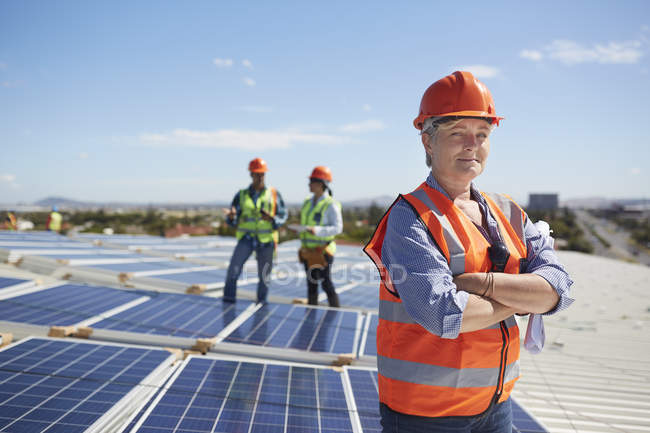 Portrait confident female engineer at sunny solar power plant — Stock Photo