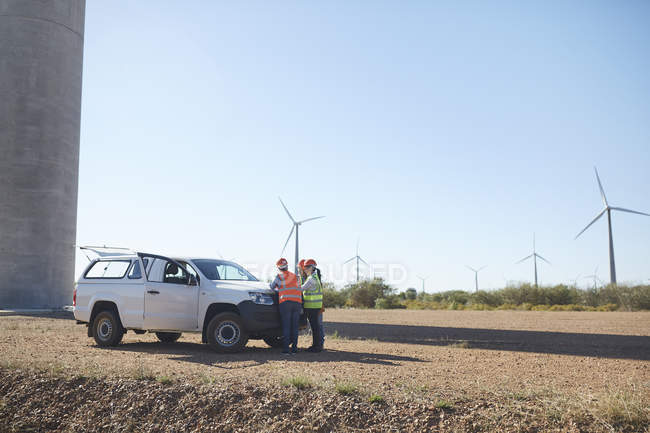 Engineers meeting at truck at sunny wind turbine power plant — Stock Photo
