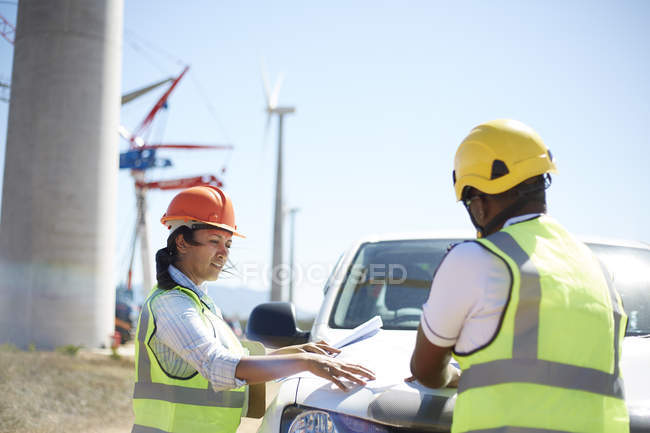 Engineers reviewing blueprints at truck at sunny wind turbine power plant — Stock Photo