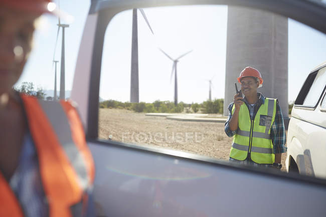 Smiling engineer using walkie-talkie at truck at sunny wind turbine power plant — Stock Photo