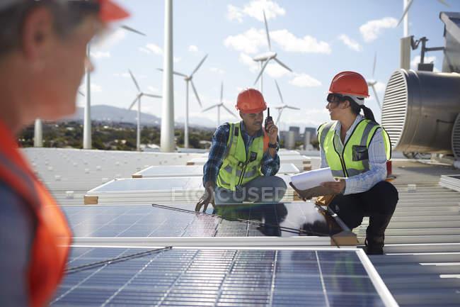 Engineers examining solar panels at alternative energy power plant — Stock Photo