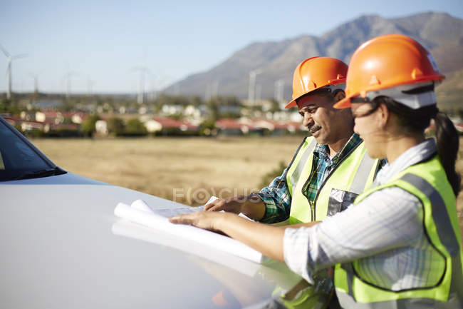 Engineers reviewing blueprints at truck at sunny power plant — Stock Photo