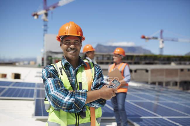 Engenheiro confiante de retrato instalando painéis solares no telhado ensolarado — Fotografia de Stock