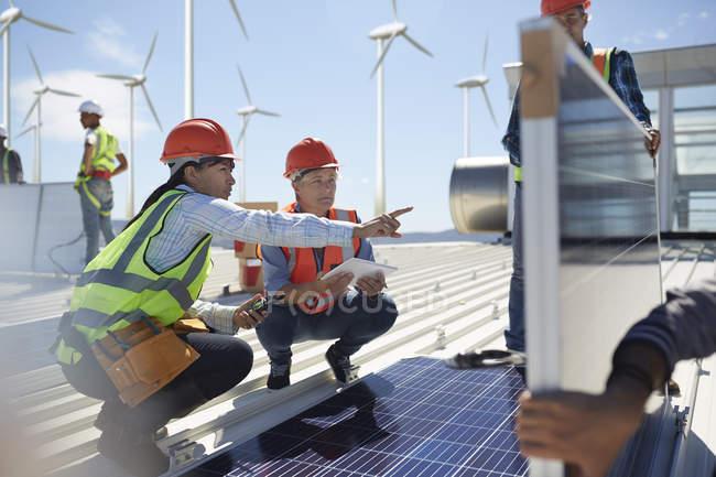 Female engineers talking, examining solar panels at power plant — стоковое фото