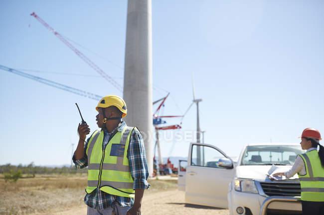 Мужчины инженер с рации на Солнечный ветер турбины электростанции — стоковое фото