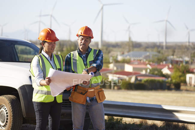 Engineers reviewing blueprints near wind turbine farm — Stock Photo