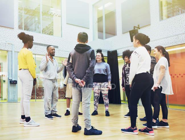 Allievi adolescenti ascoltando istruttore maschio nello studio di classe di danza — Foto stock