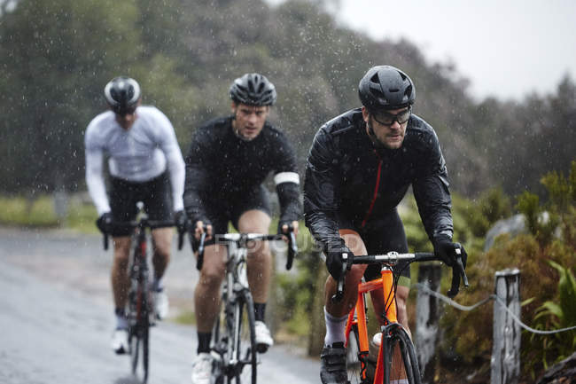 Dedicated male cyclists cycling on rainy road — Stock Photo