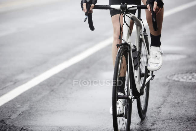Cyclist cycling on wet road, closeup — Stock Photo
