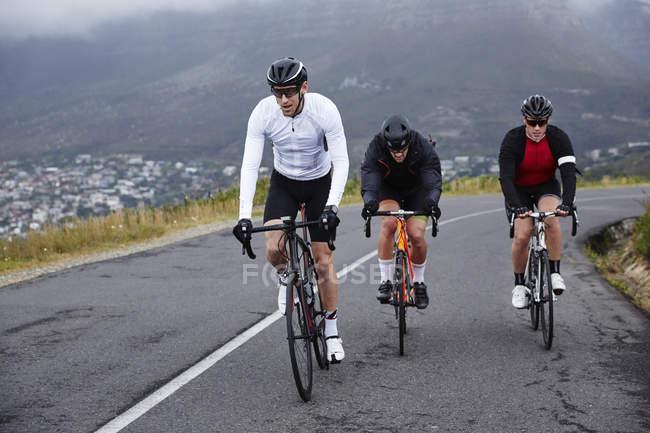 Присвячений чоловічого велосипедистів їзда на велосипеді на гору дорога — стокове фото