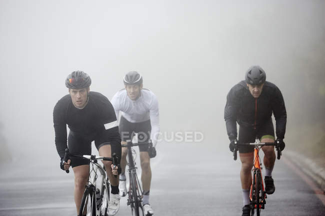 Присвячений чоловічого велосипедистів їзда на велосипеді по дорозі, дощова — стокове фото