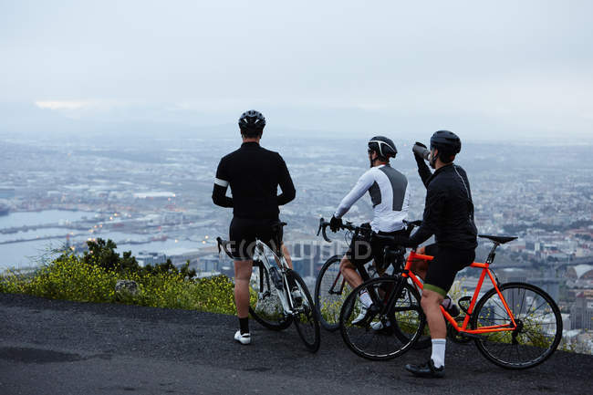 Male cyclist friends taking a break, looking at view from overlook — Stock Photo