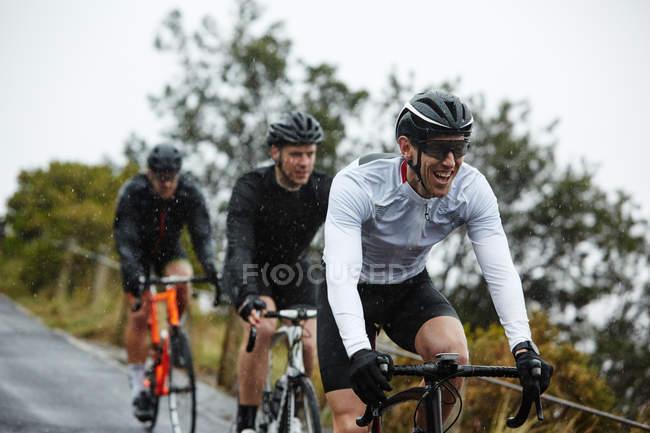 Smiling ciclista masculino de bicicleta com amigos — Fotografia de Stock