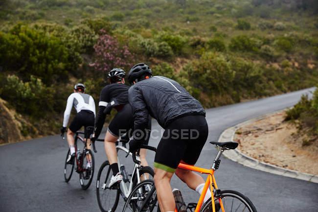 Велогонщики на велосипеде в гору по дороге — стоковое фото