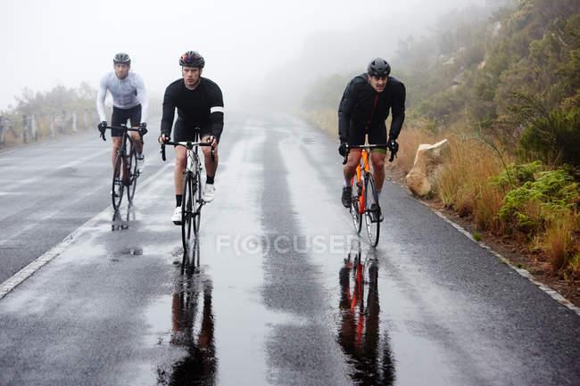 Велогонщики на мокрой дороге — стоковое фото