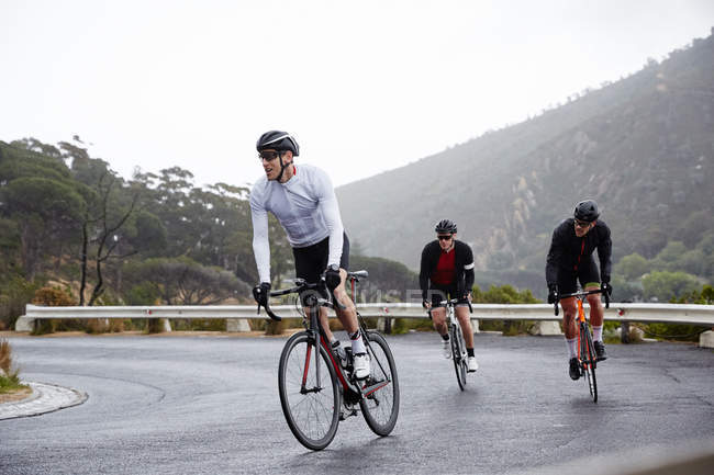 Male cyclists cycling uphill on wet road — Stock Photo