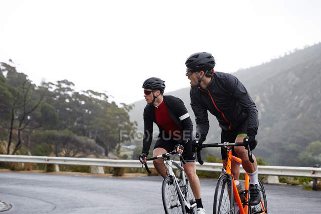 Ciclistas do sexo masculino pedalando na estrada da montanha — Fotografia de Stock