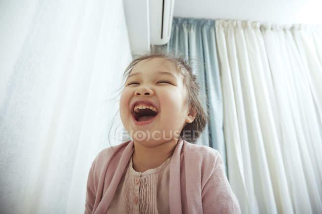 Bonito, menina dentro de casa a rir — Fotografia de Stock