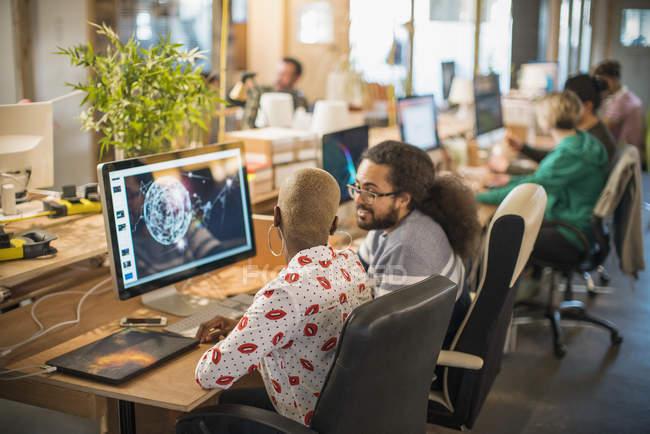 Concepteurs réunion, travaillant à l'ordinateur de bureau plan ouvert — Photo de stock