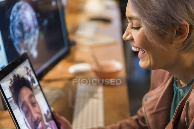 Laughing businesswoman video chatting with businessman on digital tablet — Stock Photo