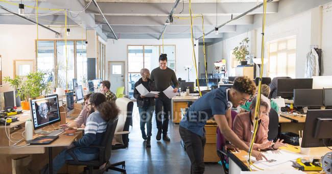 Творческие бизнесмены, работающие в офисе открытого плана — стоковое фото