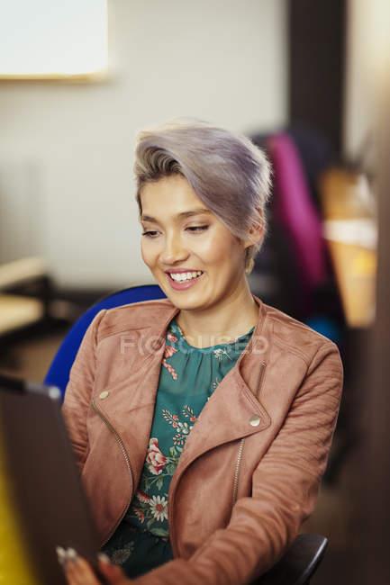 Femme d'affaires créative souriante utilisant une tablette numérique — Photo de stock