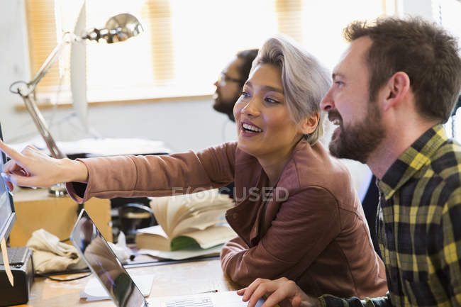 Smiling creative business people meeting, working at computer in office — Stock Photo