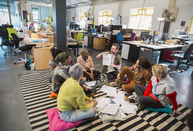 Creative business people meeting, brainstorming in circle on floor in office — Stock Photo