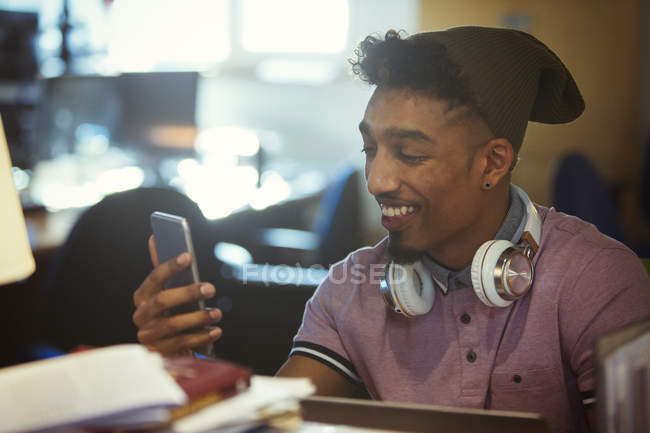 Smiling creative businessman texting with smart phone in office — Stock Photo