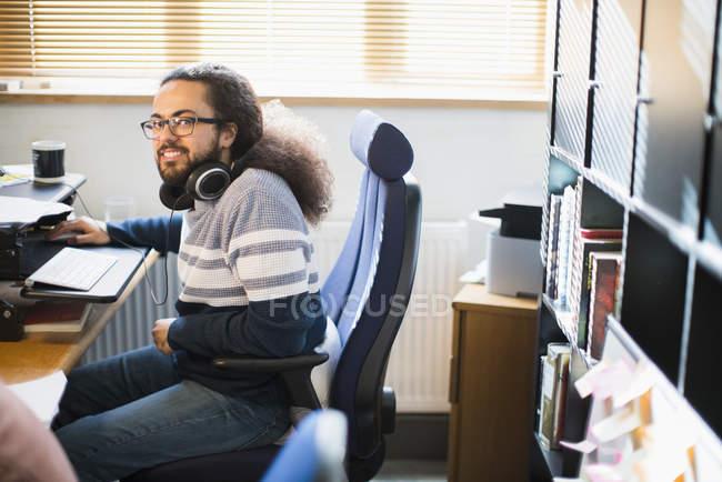 Porträt lächelnder, selbstbewusster kreativer Geschäftsmann mit Kopfhörern im Büro — Stockfoto