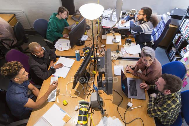 Gens d'affaires créatives travaillant, réunis à ordinateurs et portable au bureau de plan ouvert — Photo de stock