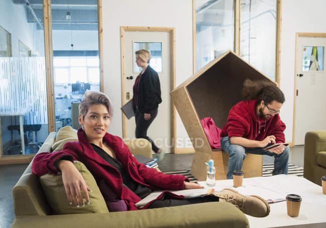 Portrait confident creative businesswoman working in open plan office — Stock Photo