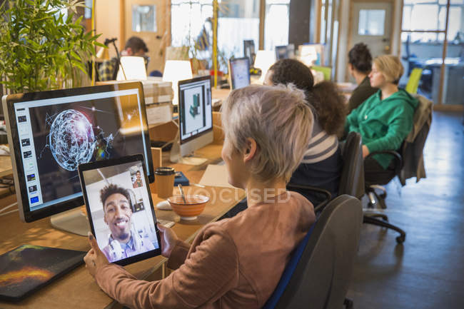 Creative businesswoman video chatting with businessman on digital tablet in open plan office — Stock Photo