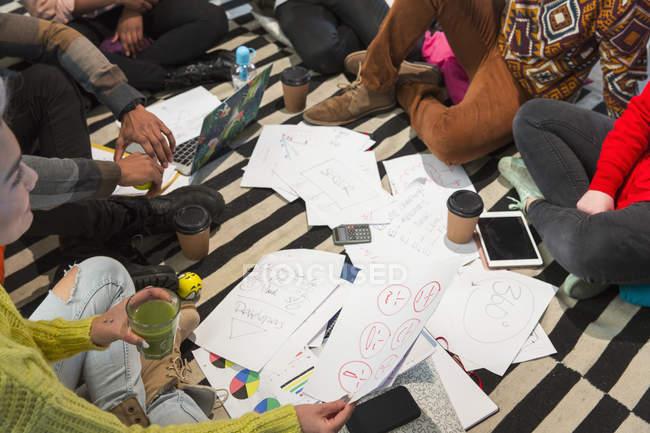 Creative business people meeting, brainstorming in circle on floor — Stock Photo