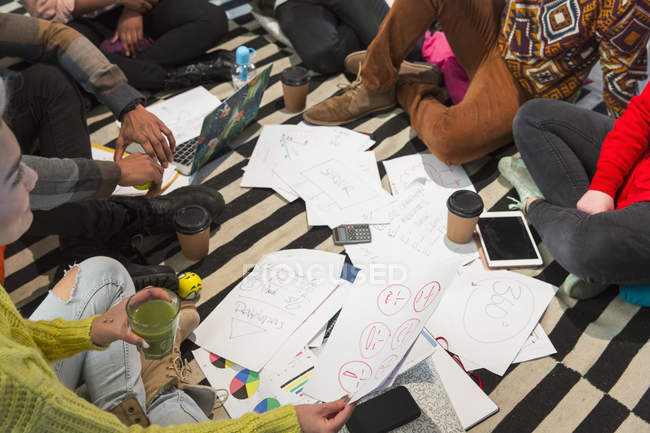 Creative business people meeting, brainstorming in circle on floor — Stock Photo