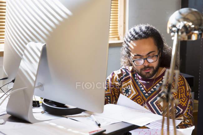 Uomo d'affari creativo concentrato che legge scartoffie al computer in ufficio — Foto stock