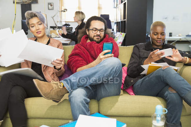 Creative business people using smart phones in office — Stock Photo