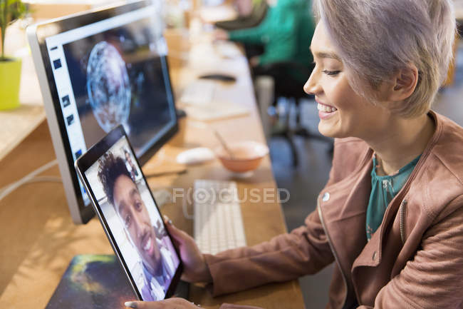 Creative businesswoman video chatting with colleague on digital tablet in office — Stock Photo