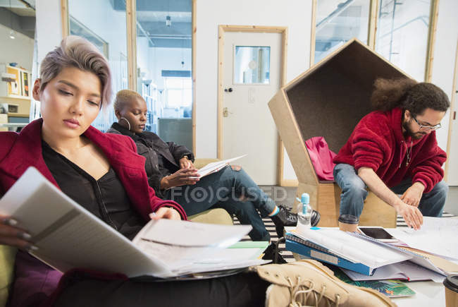 Creative business people reviewing paperwork in office — Stock Photo