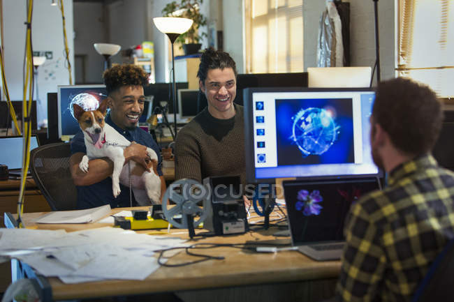 Creative business people with dog in open plan office — Stock Photo