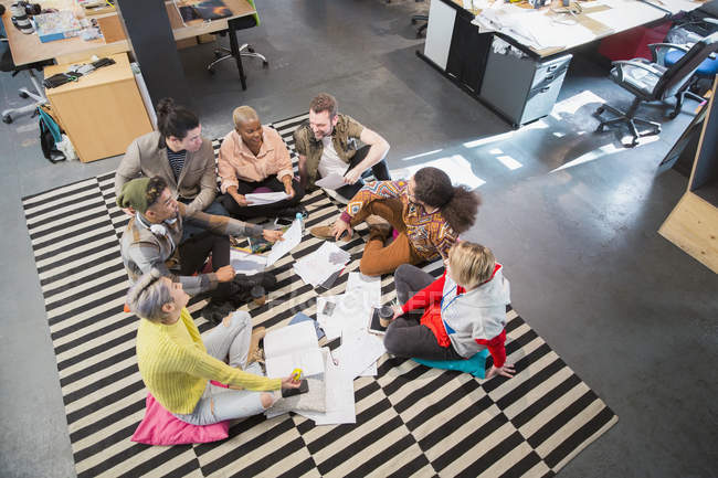 Creative business team meeting, brainstorming in circle on floor in office — Stock Photo