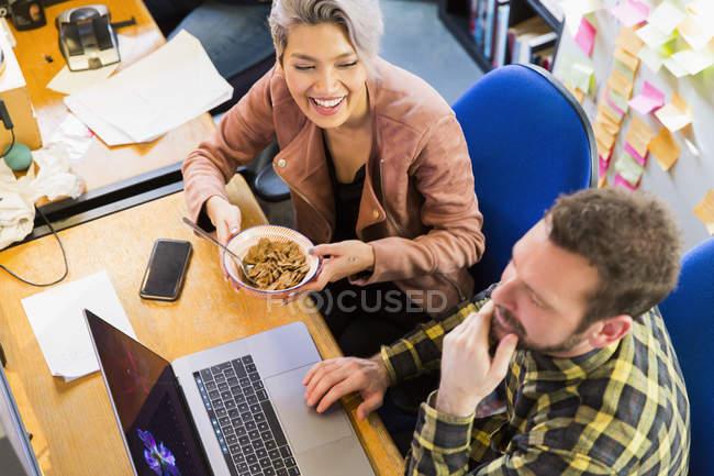 Творческие бизнесмены едят хлопья, работают за ноутбуком на работе — стоковое фото